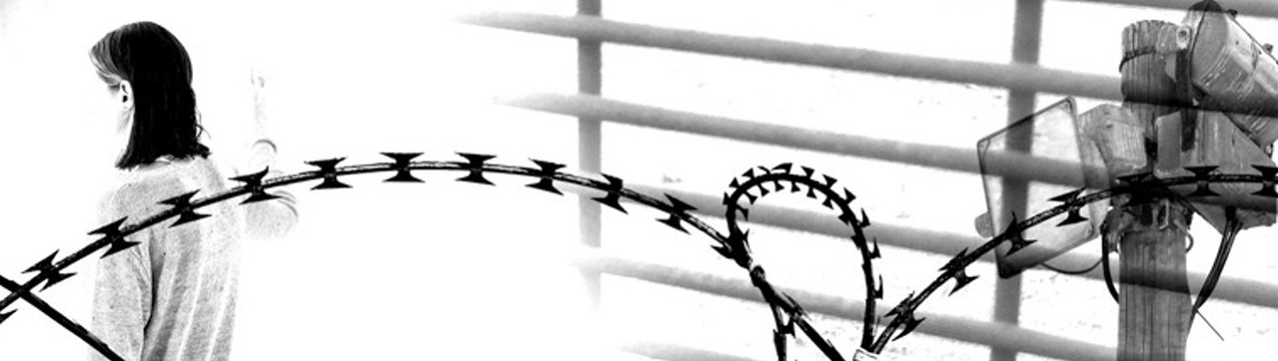 A woman in a room behind barbed wire